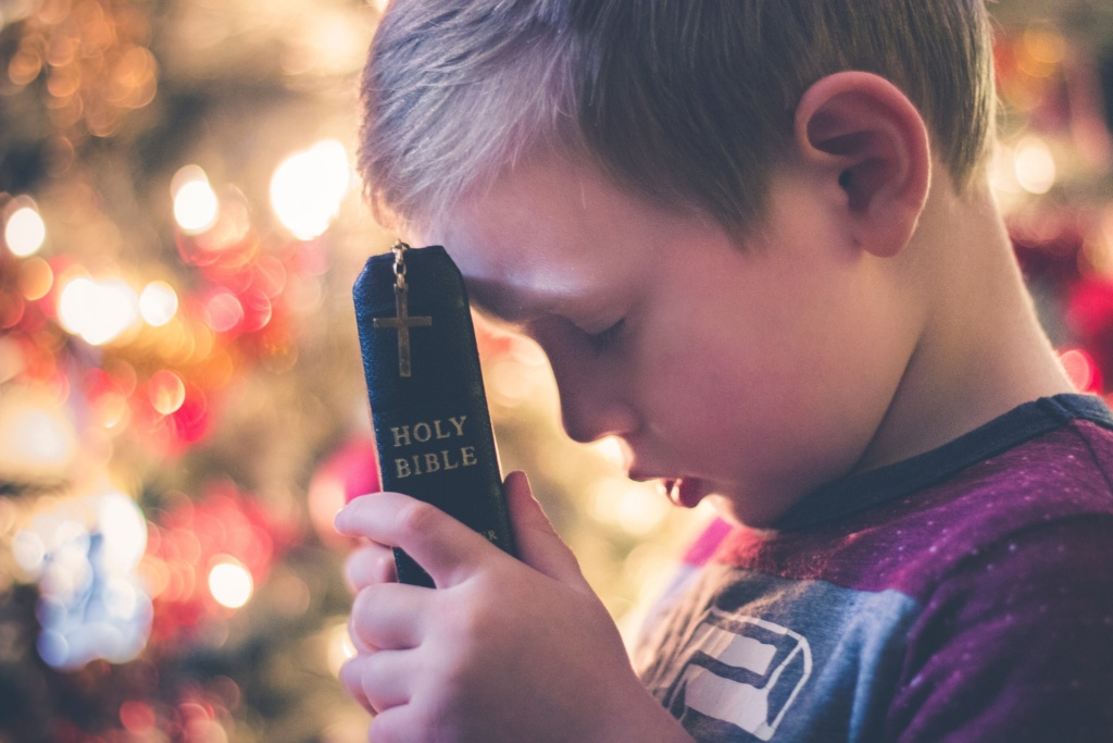 Boy at Christmas Praying with Bible