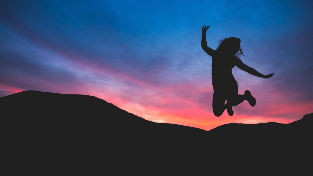 girl jumping at sunset