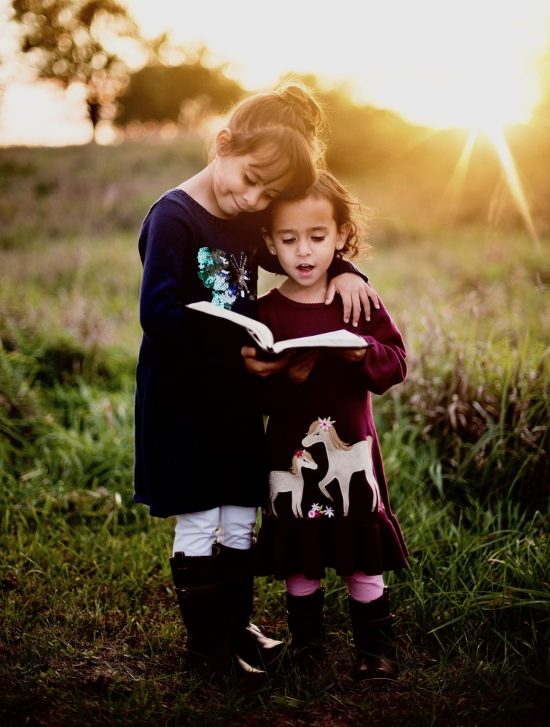 two young girls reading Bible