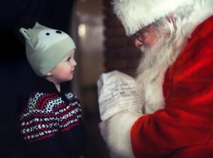 boy showing list to Santa