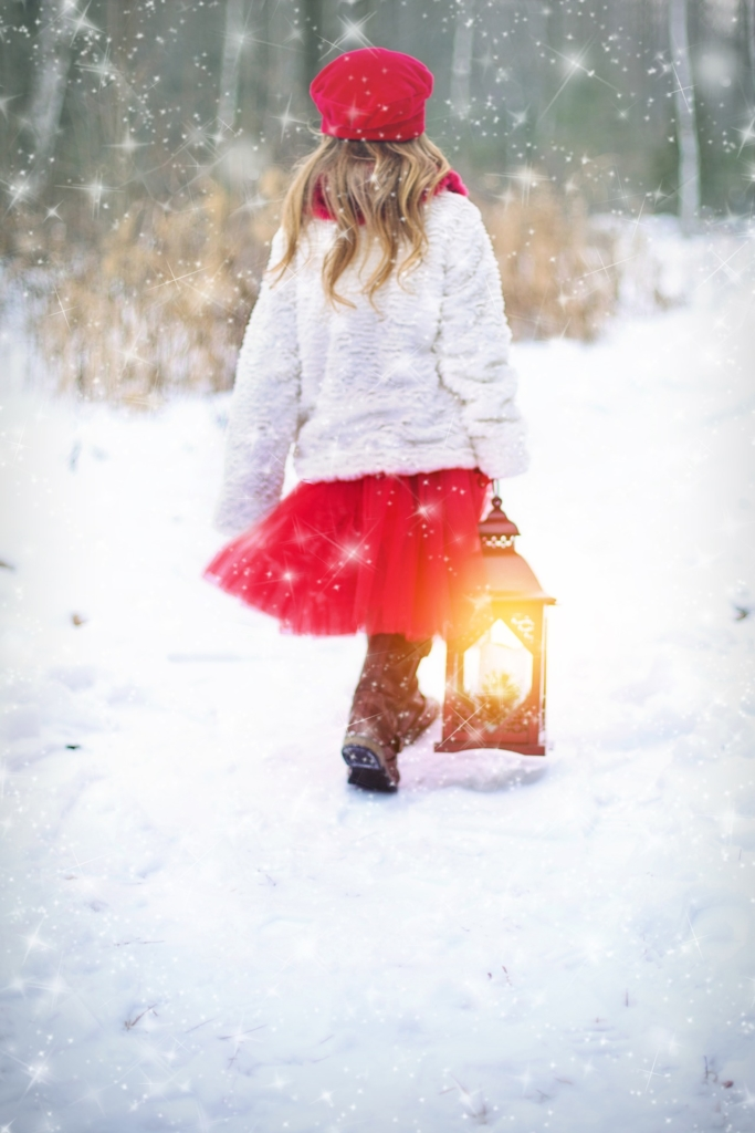 Girl in red and white carrying lantern in snow