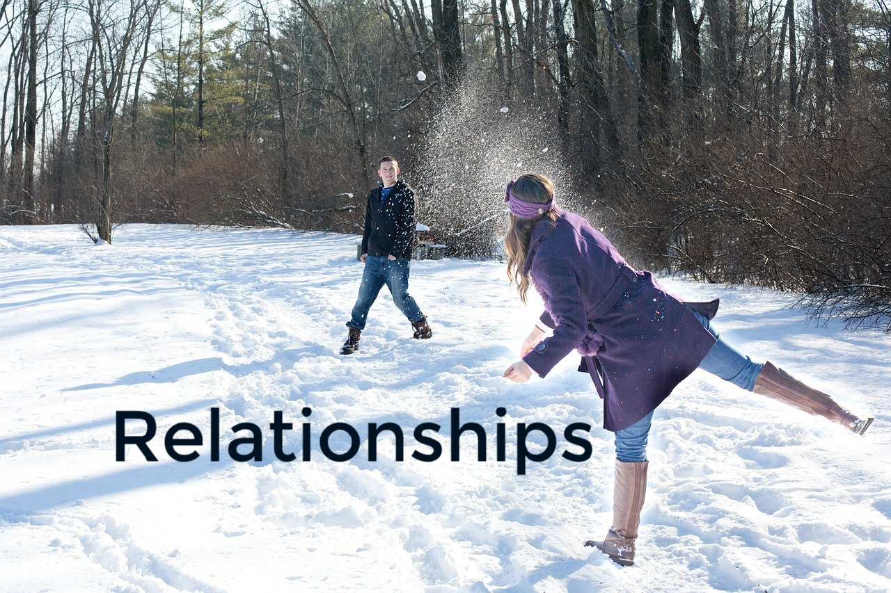 Relationships, couple having a snowball fight