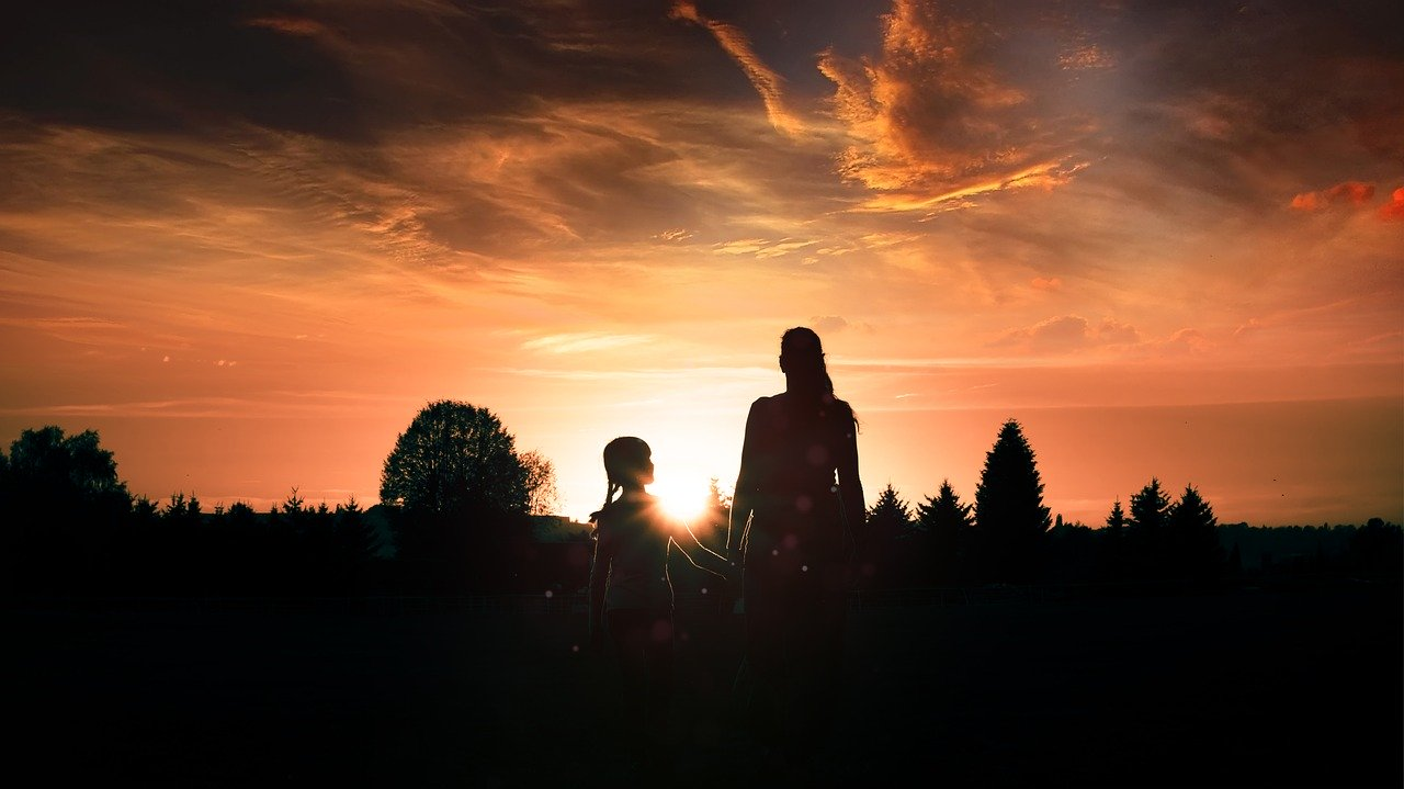 Mother and daughter watching sunset